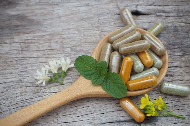 Cápsulas de ervas medicinais na mesa de madeira de ervas para um estilo de vida saudável