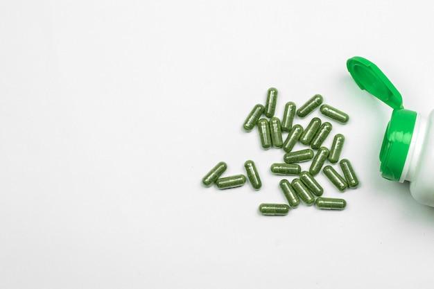 Cápsulas de ervas verdes comprimidos de ervas no fundo branco