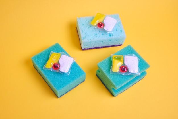 Cápsulas de gel para lava-louças e esponjas em um fundo amarelo