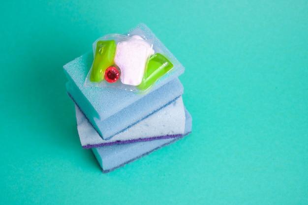 Cápsulas de gel para lava-louças e esponjas em um fundo verde