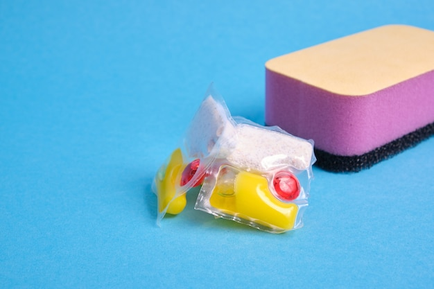 Cápsulas de gel para máquinas de lavar louça e esponjas em um fundo verde e amarelo dos locais da vista superior da cópia, a escolha entre lavar a louça com as mãos ou na máquina de lavar louça