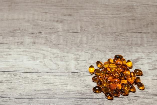 Cápsulas de gelatina macia marrom em backgroud de madeira com um copyspace