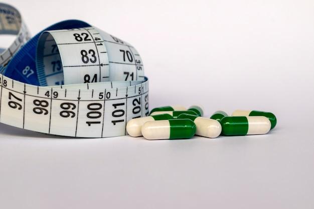 Cápsulas de medicamento e fita métrica. saúde e conceito de emagrecimento.