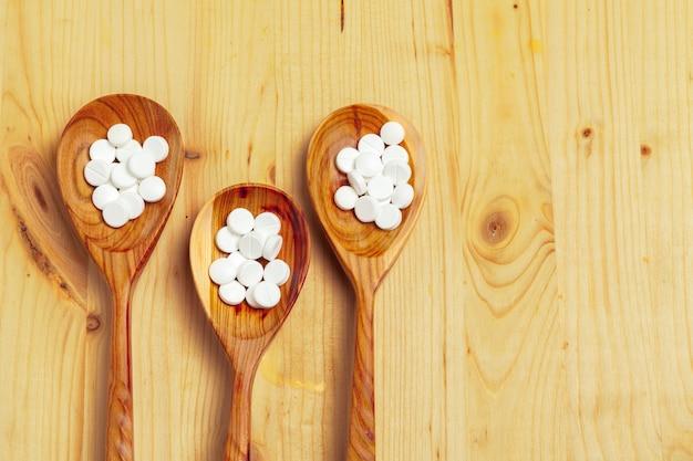 Cápsulas de medicamento, pílulas na colher de pau