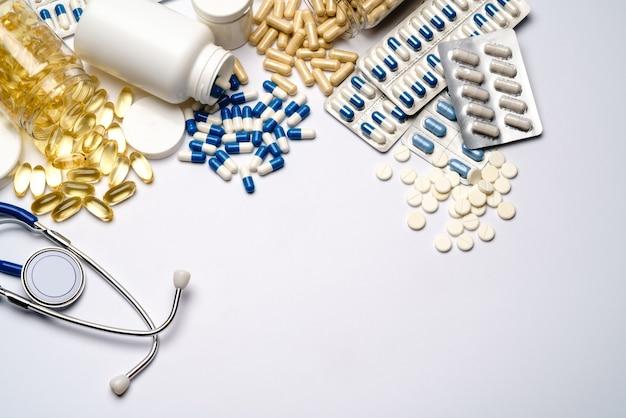 Cápsulas de medicamentos em frascos de plástico em fundo cinza claro