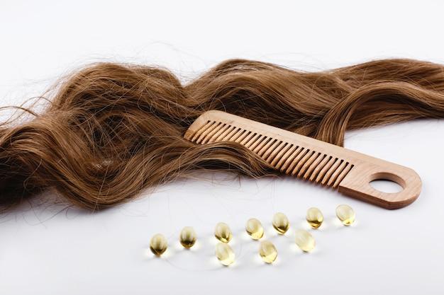 Cápsulas de óleo com vitamina e encontram-se em cachos de cabelo castanho
