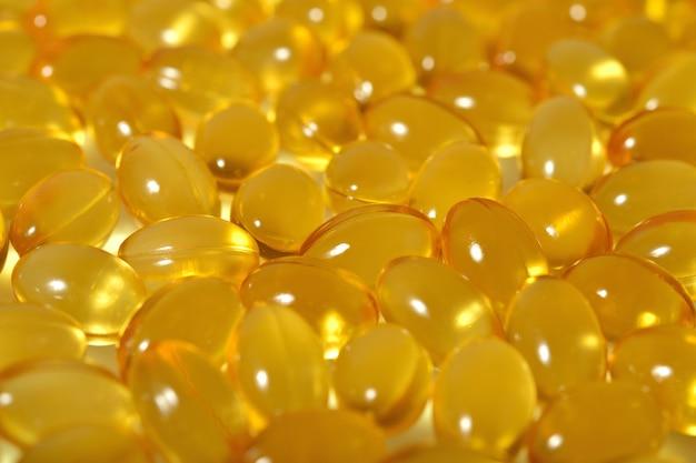 Cápsulas de óleo de gordura de peixe ômega-3 como textura de fundo. foco seletivo.