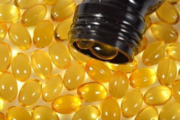 Cápsulas de óleo de gordura de peixe ômega-3 derramam da garrafa