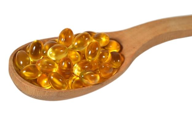 Cápsulas de óleo de gordura de peixe ômega-3 em colher de pau em um fundo branco