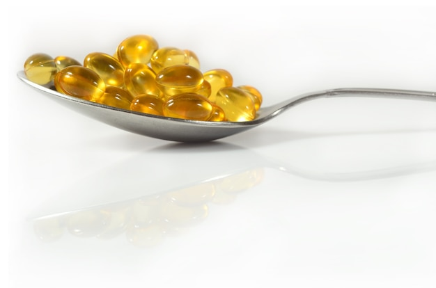 Cápsulas de óleo de gordura de peixe ômega-3 em uma colher em um fundo branco