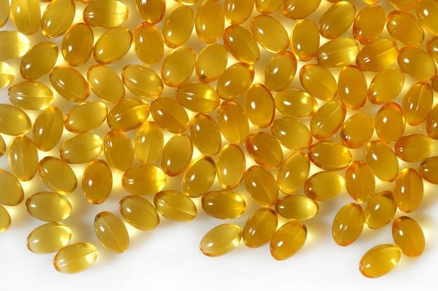 Cápsulas de óleo de gordura de peixe ômega-3 fecham-se sobre um fundo branco.