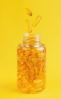 Cápsulas de óleo de peixe caindo na garrafa na parede amarela.