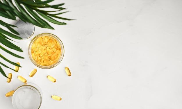 Cápsulas de óleo de peixe com ômega 3 e vitamina d em um frasco de vidro sobre uma superfície de concreto branco
