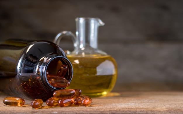 Cápsulas de óleo de peixe com ômega 3 e vitamina d em uma garrafa de vidro com textura de madeira, conceito de dieta saudável, close-up tiro.