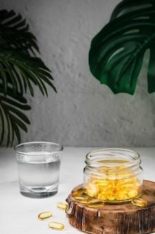 Cápsulas de óleo de peixe com ômega-3 e vitamina d em uma jarra de vidro em um suporte de madeira e um copo de água