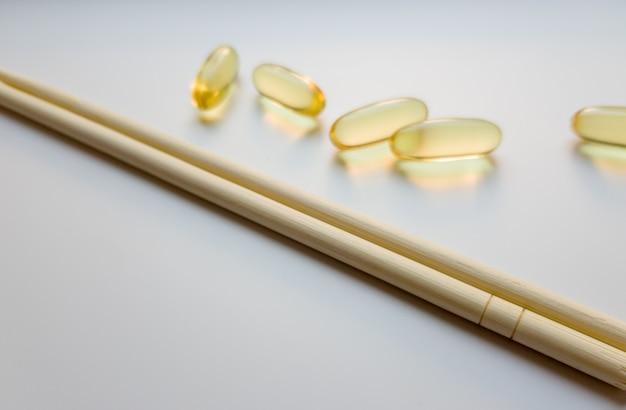 Cápsulas de óleo de peixe com pauzinhos chineses. omega 3 em um fundo branco. produto de alta resolução. suplemento alimentar. vitaminas para um estilo de vida saudável. ácido graxo. metabolismo do corpo.