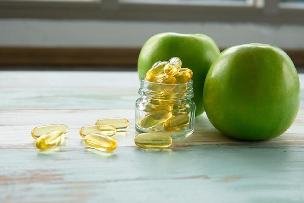 Cápsulas de óleo de peixe e maçã verde na mesa de madeira, o conceito de saúde