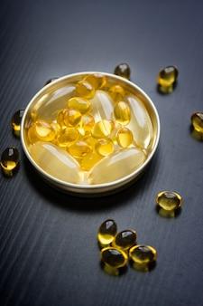 Cápsulas de óleo de peixe em copo de ouro