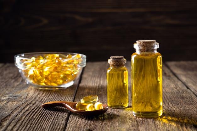 Cápsulas de óleo de peixe em fundo de madeira, suplemento de vitamina d