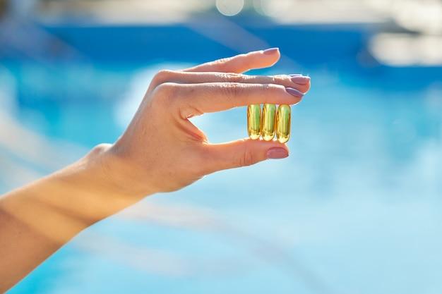 Cápsulas de óleo de peixe em mãos femininas