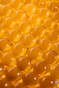 Cápsulas de óleo de peixe. muitos comprimidos redondos de cor vermelho-laranja.