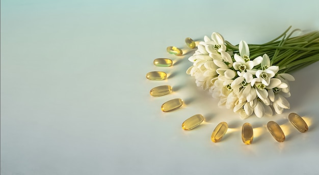 Cápsulas de óleo de peixe na superfície branca com um buquê de flores da primavera.