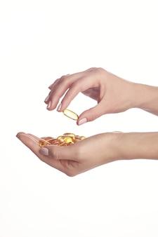 Cápsulas de óleo de peixe ômega 3 nas mãos.