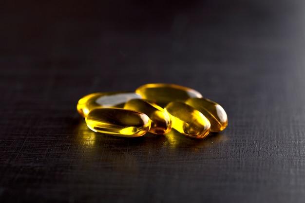 Cápsulas de óleo ômega-3 e vitamina para cuidados de saúde no quadro negro.