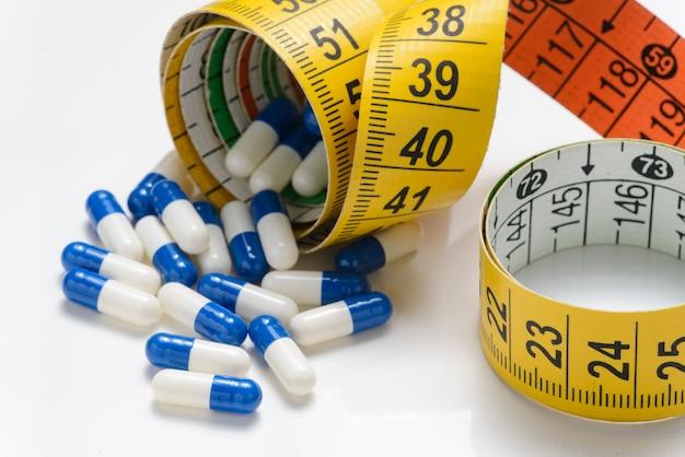 Cápsulas de remédio e fita métrica