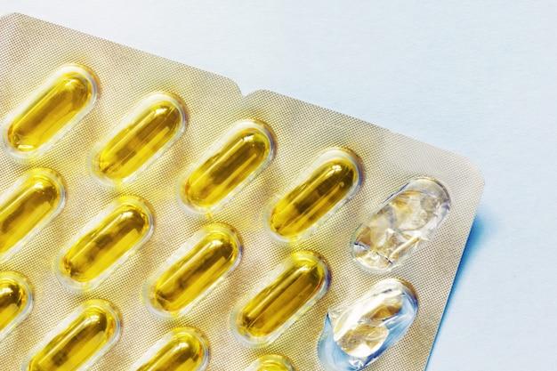 Cápsulas de softgel cheias de óleo em blister, duas cápsulas em falta. cuidados de saúde, vitaminas, suplementos conceito de ingestão diária. omega3, deficiência de vitamina d, vitamina e.
