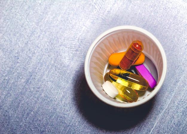 Cápsulas de suplemento alimentar e vitaminas dentro de um pequeno copo de plástico na foto macro