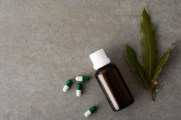 Cápsulas de vista superior com frasco de óleo em cima da mesa