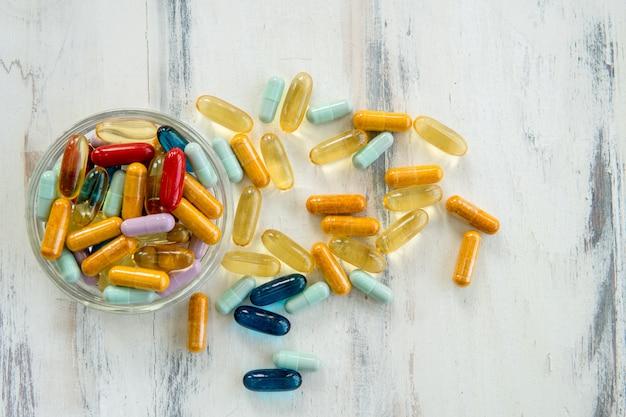 Cápsulas de vitamina coloridas no copo de vidro em madeira branca
