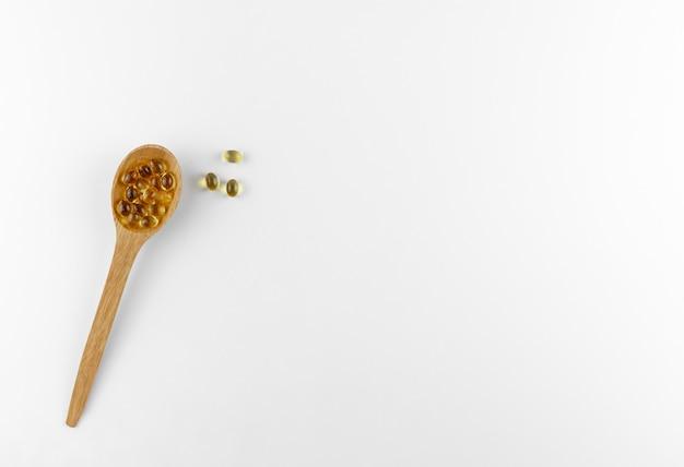 Cápsulas de vitamina d em uma colher de pau
