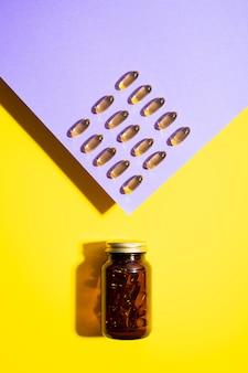 Cápsulas de vitamina d pílulas ômega em frasco de vidro em fundo amarelo lilás com sombras da moda
