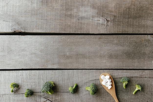 Cápsulas de vitamina ou medicamento, brócolis na colher de pau com fundo de madeira. conceito de terapia ou tratamento de saúde. comprimidos de vitamina.