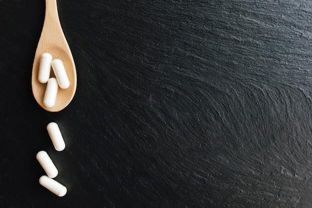 Cápsulas de vitamina ou medicamento na colher de pau em fundo preto de concreto. conceito de saúde. comprimidos de vitamina.