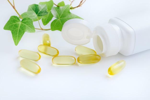 Cápsulas de vitaminas de óleo de peixe derramando do frasco de comprimidos em branco