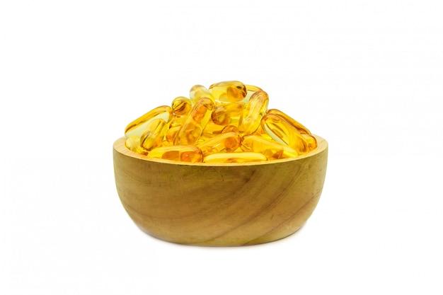 Cápsulas do óleo de fígado de bacalhau em um copo de madeira no branco.