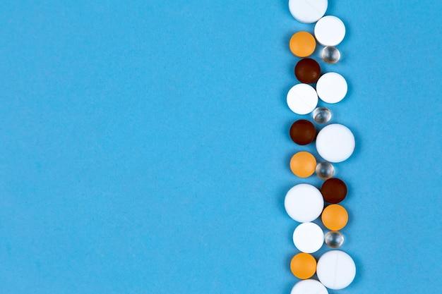 Cápsulas e comprimidos multicoloridos são dispostos sobre um fundo azul em uma fileira