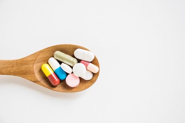 Cápsulas e comprimidos na colher de pau sobre o fundo branco