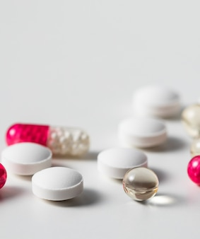 Cápsulas e comprimidos vermelhos no conceito de farmácia médica e doença de fundo branco
