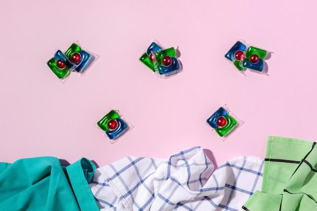 Cápsulas e toalhas de lavanderia no conceito de fundo rosa de manutenção da limpeza e higiene