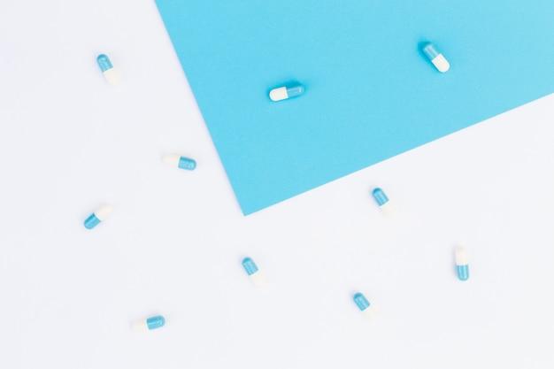 Cápsulas em fundo azul e branco