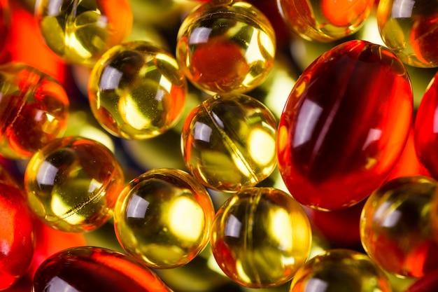 Cápsulas médicas amarelas e vermelhas em uma superfície do espelho