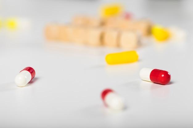 Cápsulas médicas coloridas de close-up em cima da mesa