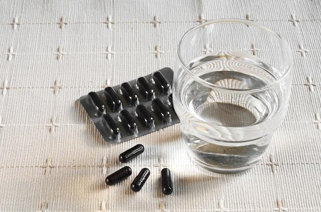 Cápsulas médicas com carvão ativado e copo de água na toalha de mesa