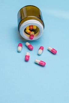 Cápsulas medicinais vermelhas e brancas são derramadas de um frasco de vidro