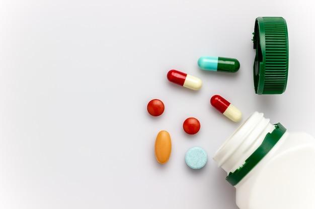 Cápsulas multicoloridas com frascos de medicamento branco e tampas verdes sobre fundo branco