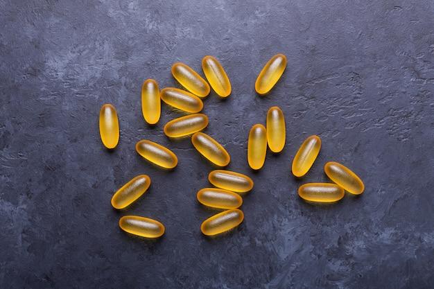 Cápsulas omega 3 no fundo de pedra escura close up conceito de cuidados de saúde